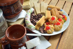 Have breakfast at home with tea and biscuits. Closeup of a plate filled with cookies of various kinds. Near a teapot and a cup Royalty Free Stock Images
