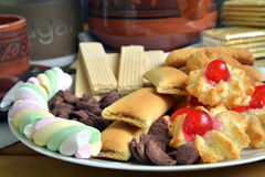 Have breakfast at home with tea and biscuits. Closeup of a plate filled with cookies of various kinds. Near a teapot and a cup Royalty Free Stock Photos