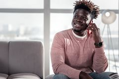 Cheerful international man having rest after work. Have business. Kind male expressing positivity while holding telephone near his ear stock images