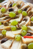 Have a canape?. Delicious canapes with grapes, cheese and olives Royalty Free Stock Photos