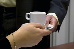 Have a coffee. Business man giving a cup of coffee to a business woman royalty free stock image