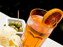 Have a drink. Longdrink with chips and green olives royalty free stock photos