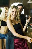 Have a drink with us!. Young fresh people in the bar, a man and two women, inviting you to stay for a drink, their treat Stock Photography