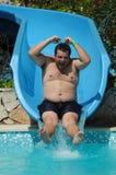 Have fun on aqua park. Happy fat man have fun on aqua park Royalty Free Stock Photography