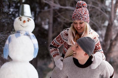 Have fun and laughs next to the snowman Royalty Free Stock Photos