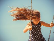 Girl swinging on swing-set. Have fun and leisure concept. Long haired enjoyable girl swinging outdoor in garden playground. Lovely child playing on swing-set royalty free stock photography