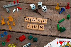 `Have Fun` made from Scrabble game letters. Risk, Battleship pieces, Monopoly, Settler of Catan and other game pieces stock images