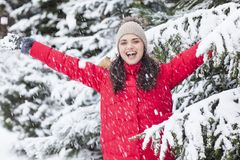 Beautiful woman is happy while is snowing in the park. Have fun during the winter season. World is more beautiful when is snowing around Stock Images
