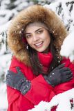 Beautiful woman is happy while is snowing in the park. Have fun during the winter season. World is more beautiful when is snowing around Royalty Free Stock Photos