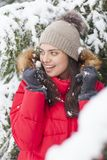 Beautiful woman is happy while is snowing in the park. Have fun during the winter season. World is more beautiful when is snowing around Stock Photography