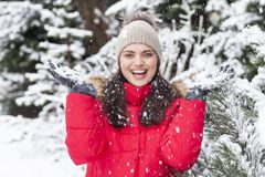 Beautiful woman is happy while is snowing in the park. Have fun during the winter season. World is more beautiful when is snowing around Royalty Free Stock Photo