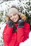 Beautiful woman is happy while is snowing in the park. Have fun during the winter season. World is more beautiful when is snowing around Royalty Free Stock Photography
