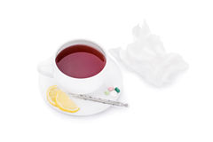 Have this and get better. Cup of tea with pills, some lemon, a thermometer and some wrinkled napkins isolated on white background stock photos