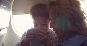 They have good time with smart phone in plane. In the plane. Grandmother telling something to the grandchild while he using smartphone to entertain himself stock video