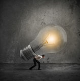 Have a great idea to be realized. Businessman holds a big light bulb. Have a great idea to be realized concept Royalty Free Stock Photo