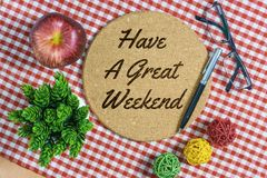 Have a Great Weekend. Warm Greeting on Round Bulletin Board. Have A Great Weekend. Cork bulletin board on red stripes napkin with pen, apple, spectacle and Royalty Free Stock Image