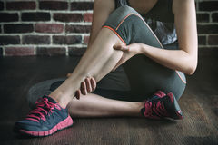 Have a leg cramp in fitness exercise training, healthy lifestyle. Concept, indoors gym wooden floor brick wall background stock photo