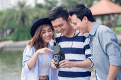 Have a look. Copy-spaced image of happy friends having fun with vintage photo camera outside Stock Photos