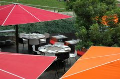 Have lunch. Terrace with orange and red umbrellas Royalty Free Stock Photography