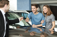 They have made a right vehical choise. Young car salesman giving Stock Images