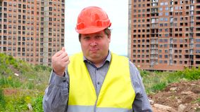 Have a money concept. Builder making cash sign gesture rubbing fingers together on construction site background.  stock video