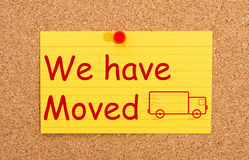 We have moved. A yellow index card on a cork board with the words we have moved on it Royalty Free Stock Photography