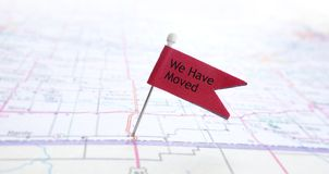 We Have Moved. Closeup of red pin flag on a map with We Have Moved text Stock Photography