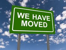 We have moved. Green highway sign with text we have moved against blue sky and clouds Stock Photos