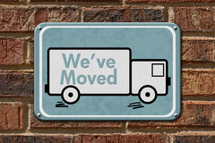 We have Moved Sign. A blue sign with the word We've Moved with a truck on a brick wall Stock Image