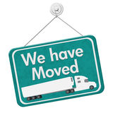 We have Moved Sign. A teal hanging sign with text We Have Moved with a truck isolated over white Royalty Free Stock Photography