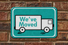 We have Moved Sign. A teal sign with the word We've Moved with a truck on a brick wall Stock Photography