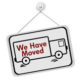 We Have Moved Sign. A white and black sign with the words We Have Moved and a truck isolated on a white background, We Have Moved Sign Royalty Free Stock Photo