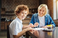 Excited curly haired child enjoying spending time with granny. We have so much fun. Selective focus on a smart preteen grandson turning his head into the camera royalty free stock images