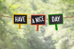 Have a nice day on board. Have a nice day written on color small chalkboard linked rope with clothespin on nature green bokeh light background royalty free stock images