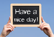 Have a nice day - female hands holding chalkboard with text. Blue sky in the background royalty free stock photo