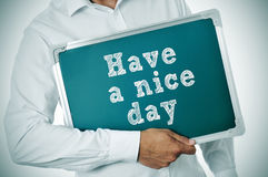 Have a nice day. Man holding a chalkboard with the sentence have a nice day written in it royalty free stock photography