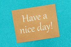 Have a nice day message on a brown greeting card. Of teal glitter paper stock image