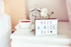 Have a nice day message on lighted box, alarm clock, cup of coffee and flower on the bedside table in sun light. Good morning mood royalty free stock image