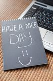 Have a nice day. Spiral notebook on which words a nice day. A laptop. Improving sentiment Royalty Free Stock Photo