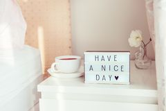 Have a nice day text message on lighted box, cup of coffee and white flower on the bedside table in sun light. Good morning mood. stock image
