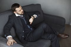 Worried Man with Watch. We have no more . Portrait of the handsome serious bearded young man in trendy suit sweater and white shirt, sitting on sofa, looking at stock photos