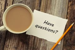 Have questions Inscription on white blank paper with pencil and cup of coffee. Rustic wooden background. Top view royalty free stock images