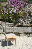 Have a Seat. Old chair sitting in the sand with flower bed in the background Royalty Free Stock Photo