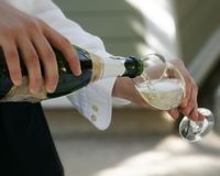 Have some Champagne. A pour of champagne at a private dinner party Royalty Free Stock Photos