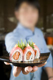 Have some sushi. Japanese sushi chef holding out a plate of sushi to camera Royalty Free Stock Photography