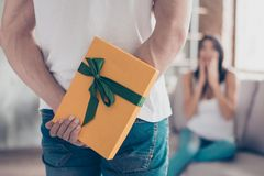 Have something for you, dear!  Focus on a yellow gift box, shock. Ed brunette girlfriend on background is waiting for surprise from back of her lover Royalty Free Stock Photography