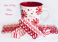 Have A Very Merry Christmas. This is a delicious red and white striped old fashioned peppermint ribbon Christmas candy and a red & white holiday cup stock image