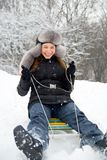 Have a winter fun!. Laughing girl in winter clothing goes down on sleds down the hill Royalty Free Stock Images