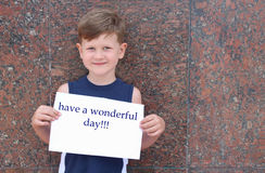 Have a wonderful day. A todler cute smiling and holding a poster with an inscription .a small boy wishes a good day Royalty Free Stock Image