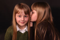 Have you heard?. Young twin girls share a secret whisper stock photos